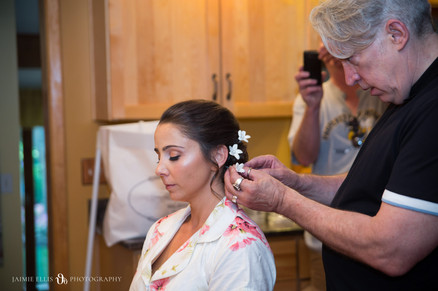 bride getting her hair done with flower accents