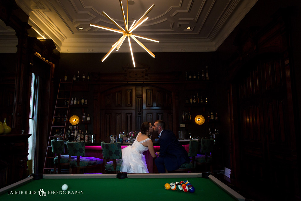 bride and groom kissing in bar at Delaware Mansion in Buffalo NY