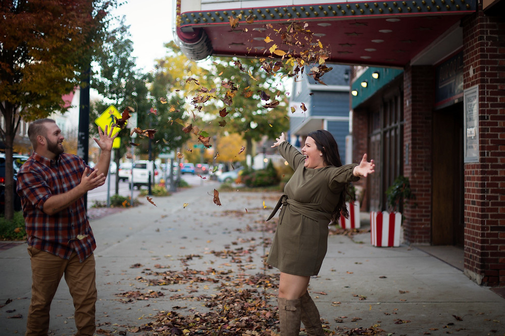 throwing leaves fall engagement photo session East Aurora Theater Main St