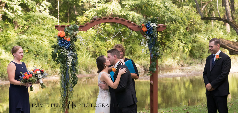 bride and groom first kiss at wedding ceremony at O'Brien's Sleepy Hollow in East Aurora NY