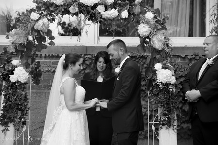 bride and groom emotionally share rings at Mansion on Delaware wedding ceremony in Buffalo NY
