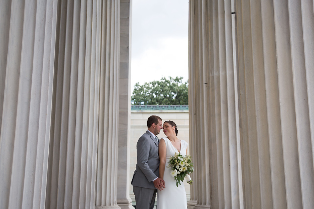 bride and groom in columns at Buffalo's Albright Knox Art Gallery in Delaware Park