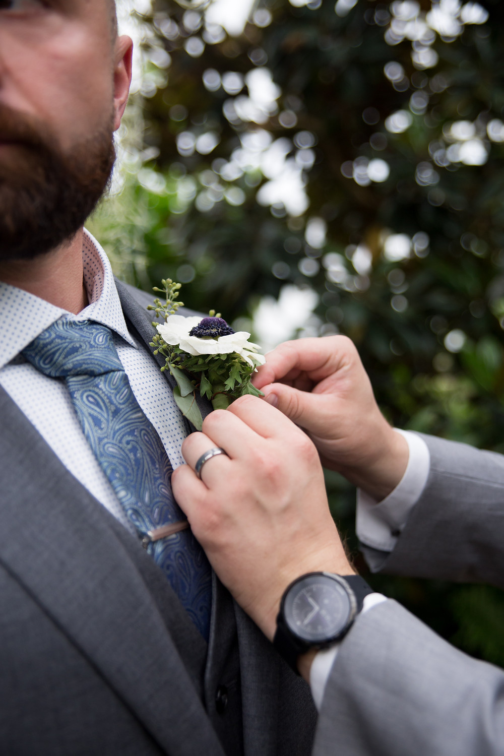 groomsman putting on groom's boutonnière at Buffalo Botanical Gardens