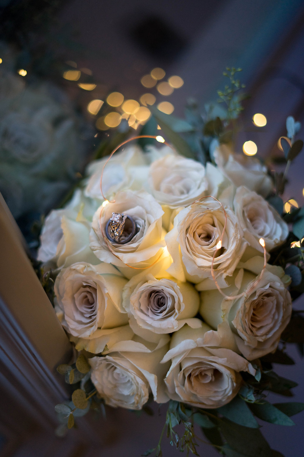 white rose bouquet and wedding rings with twinkle lights