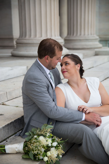 bride and groom on steps at Buffalo's Albright Knox Art Gallery in Delaware Park