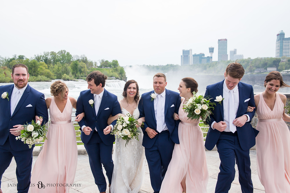 wedding party laughing and walking with bride and groom at Niagara Falls State Park NY USA photo