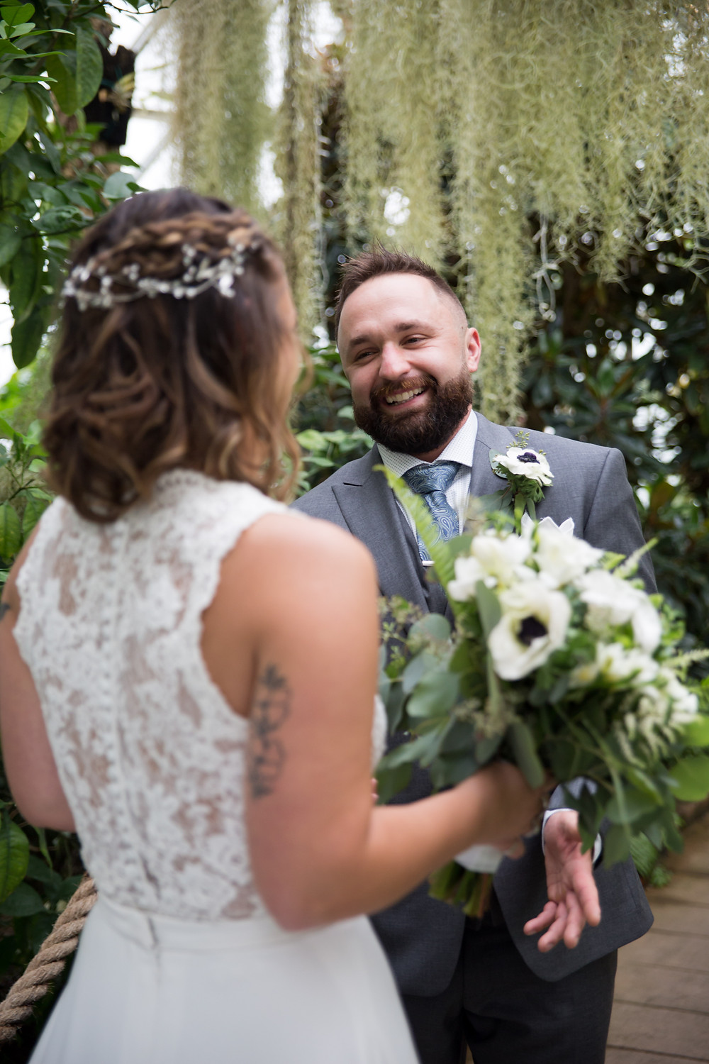 happy groom during first look inside Buffalo Botanical Gardens