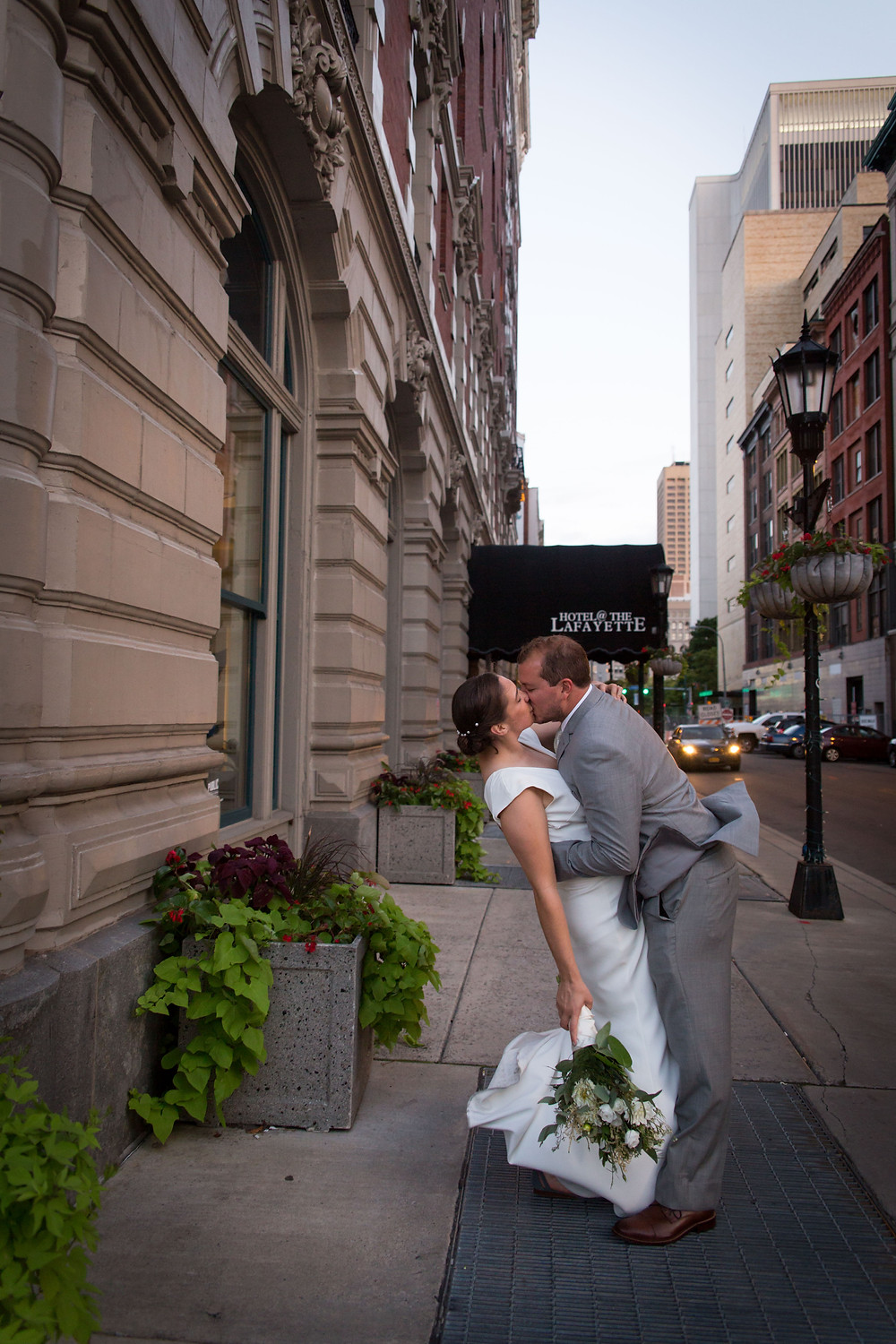 bride and groom outside Buffalo's Hotel Lafayette at sunset kissing