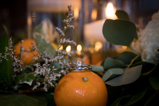 orange and floral wedding centerpiece with rings