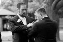 groomsmen help each other with boutonniere pinning at Niagara Falls State Park NY USA before wedding ceremony