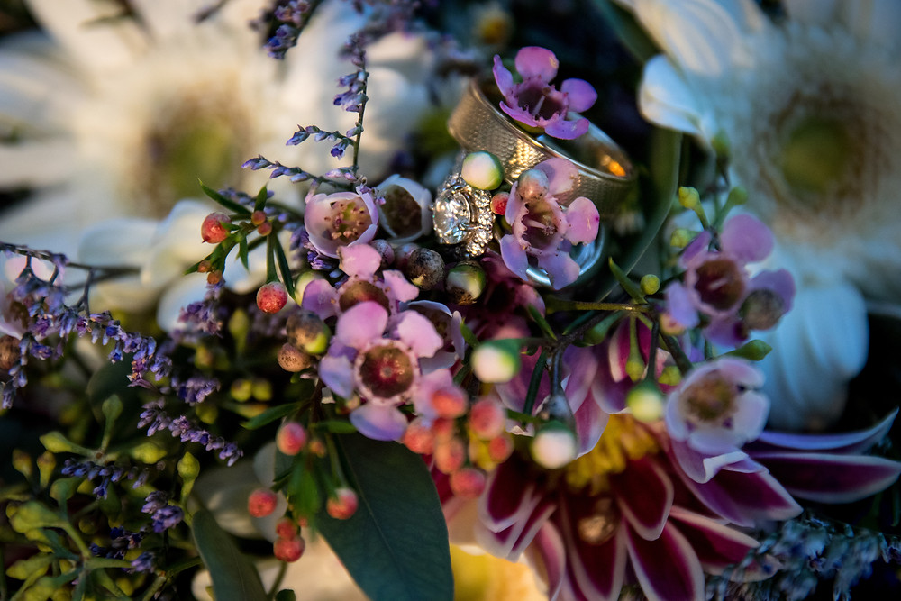 wildflower bouquet with wedding and engagement rings detail photo