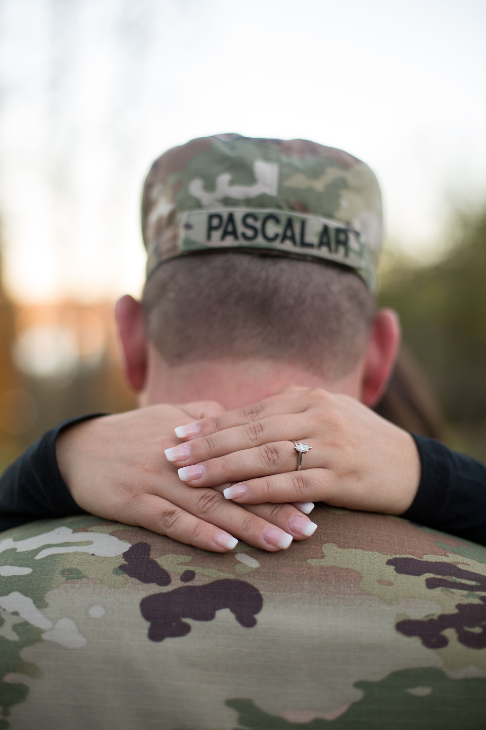 hands with diamond engagement ring around neck of army man in uniform