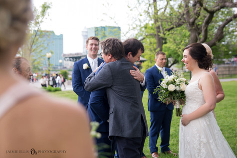 dad hugging groom while giving away his daughter the bride during wedding ceremony at Niagara Falls State Park NY USA