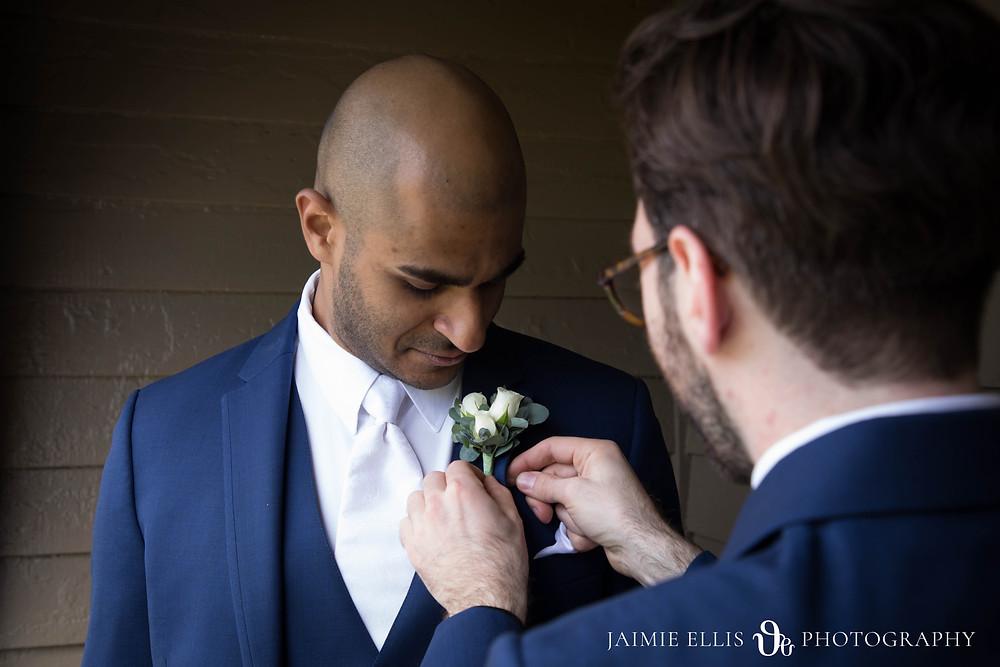 groomsmen puts boutonniere on groom Buffalo NY