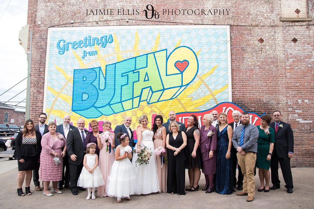 big family group shot and wedding party at greetings from Buffalo postcard mural in downtown Buffalo NY