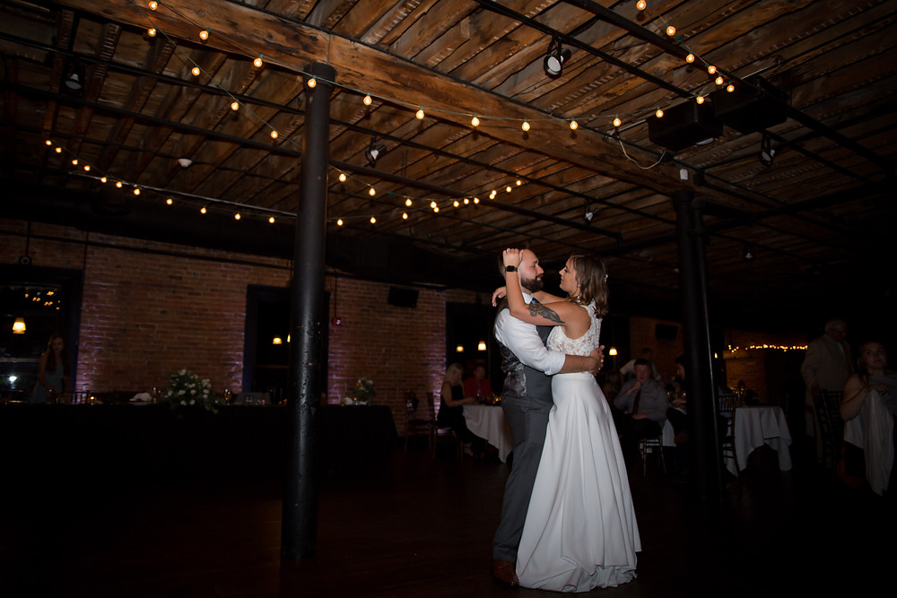 bride and groom first dance inside dark and moody Buffalo venue Pearl St Grill