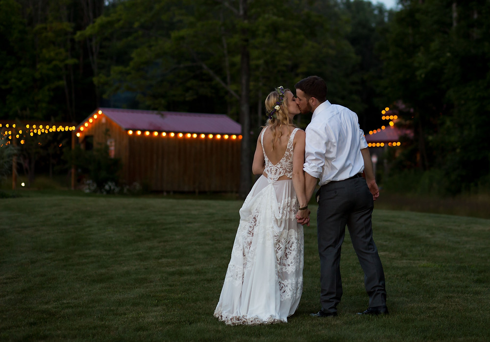 bride and groom kissing with barns lit up in background at La Esposita Bonita Wedding