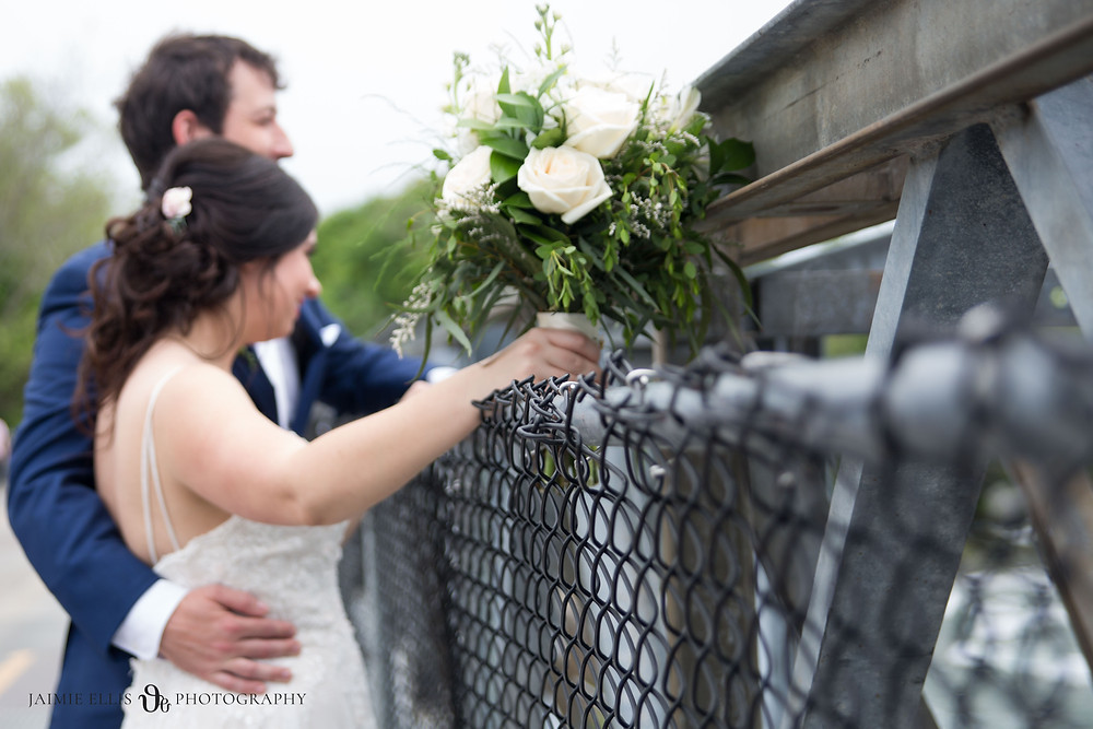Niagara Falls NY USA Wedding Photo on the Bridge to Goat Island with bride holding the chain link fence and her bouquet