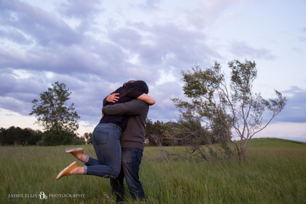 happy hugging couple at Tifft Nature Preserve in Buffalo NY for golden hour engagement session