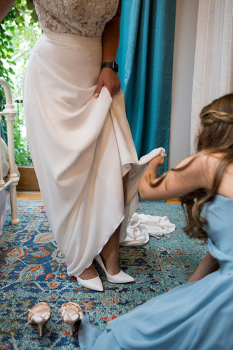 bridesmaid helping bride into shoes - 13 must have getting ready photos on your wedding day