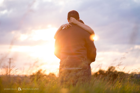 happy kissing couple at Tifft Nature Preserve in Buffalo NY for golden hour engagement session