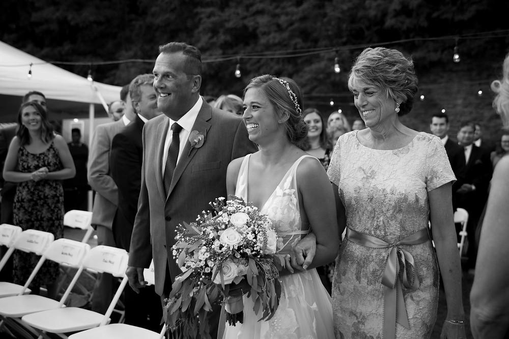 bride walking down aisle with parents at Heron Hill Winery Keuka NY