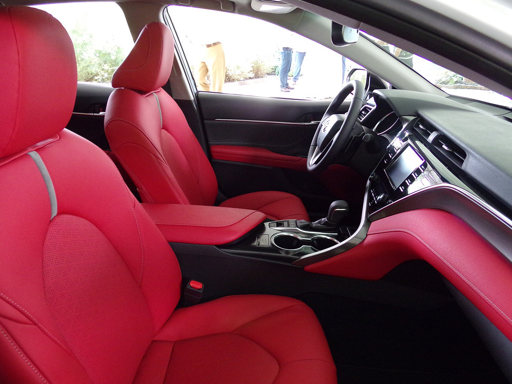 The red leather interior evokes comparison to Bentley interiors.