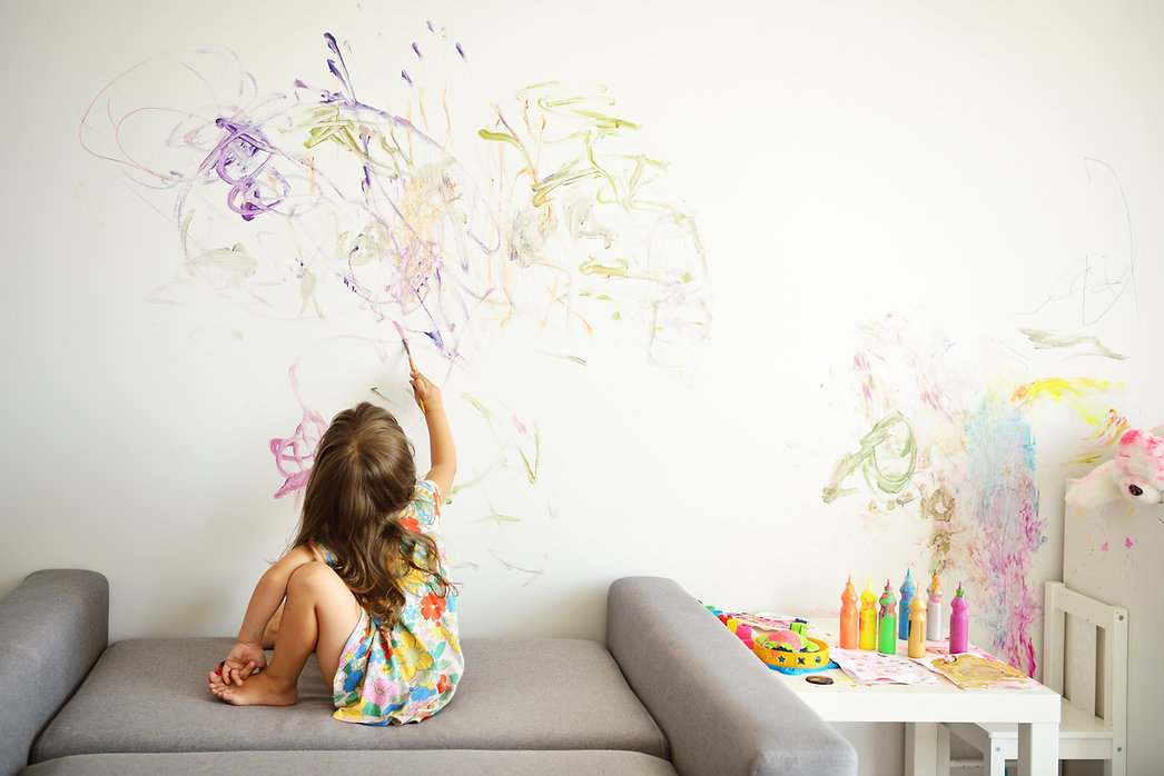 Curly cute little toddler girl painting