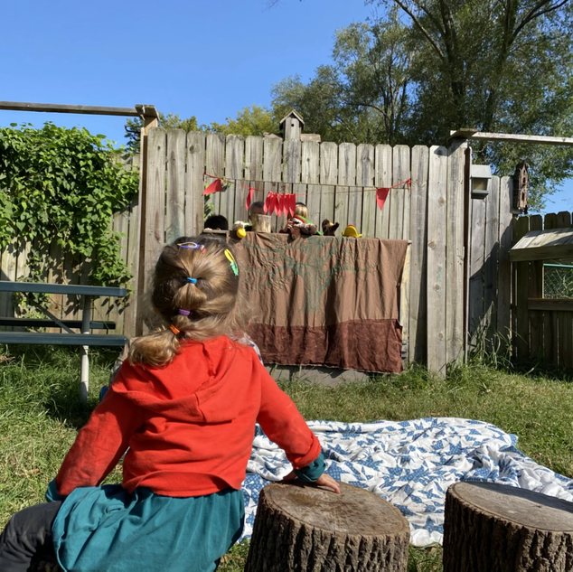 Eleanor enjoying a child led and performed puppet show