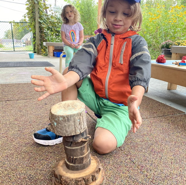 Luke building a tower with tree cookies