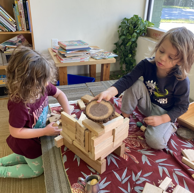 Luke and Moxie building with wooden blocks and tree cookies