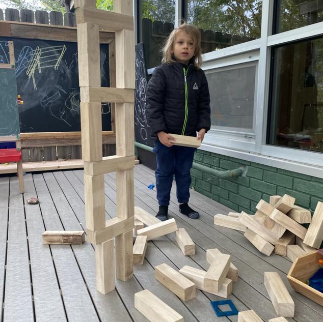 Luke next to his tall block tower