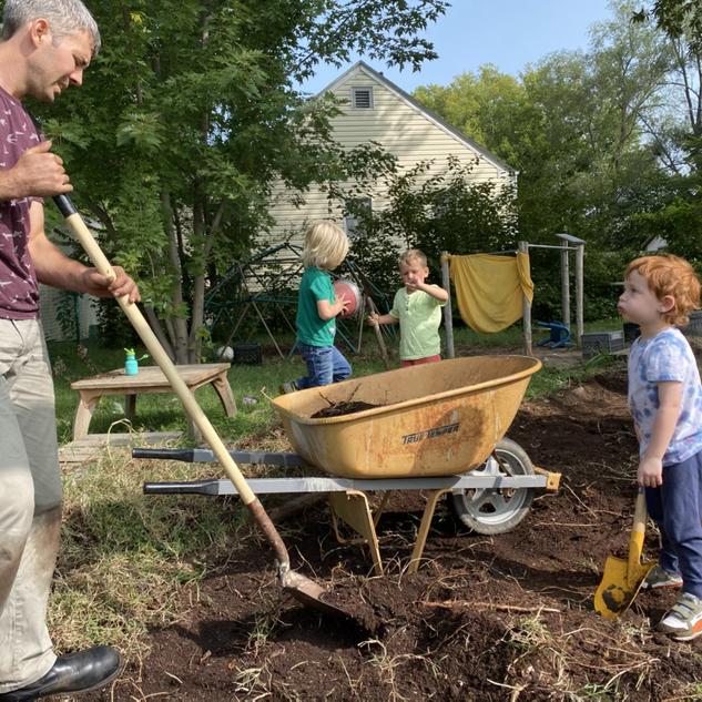 Dolan, Nico, and Harry helping Matt move mulch to make room for a sandbox