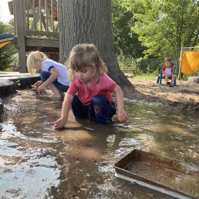 Eleanor loving the water in the sandbox