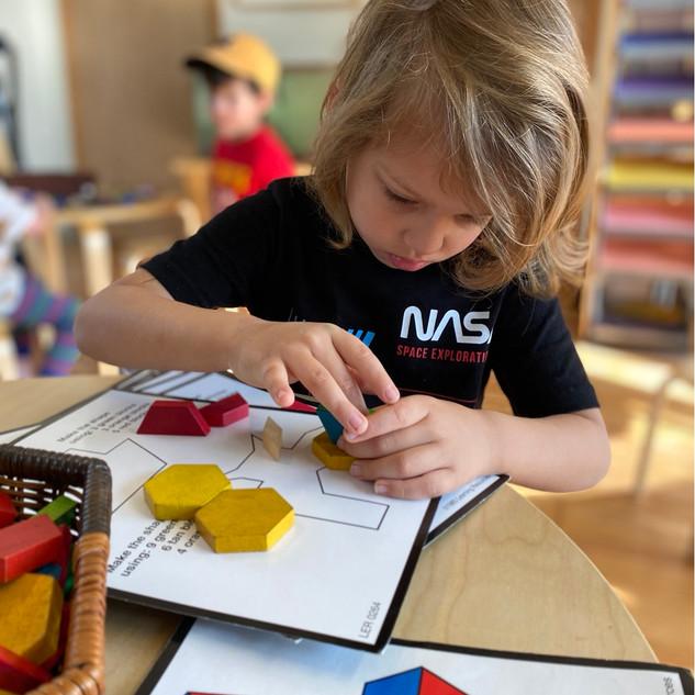 Luke using our geometic blocks to create designs