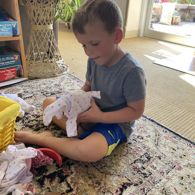 Nico dressing a baby doll
