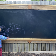 Eleanor drawing in the outdoor classroom
