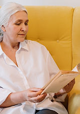 an-elderly-woman-sitting-on-a-couch-read