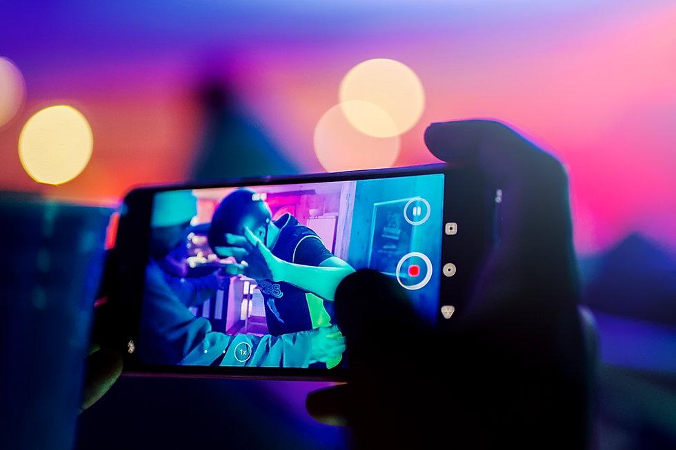Un client filme avec son smartphone un jeune qui tente de rester debout sur un snowboard GET X COLD, lors d'une soirée évènelmentielle de la marque