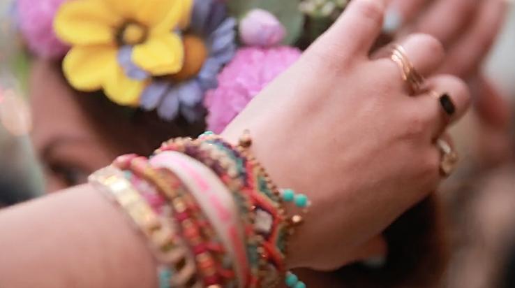 jeune fille avec des fleurs dans les cheveux et des bracelets multicolores