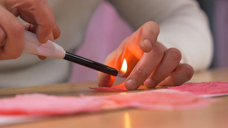 Les mains du créateur William Amor qui chauffent des matières recyclées pour leur donner des formes de pétales de fleurs. Upcycling.