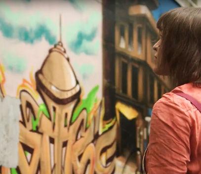 Une jeune femme regarde du street art dans les rues de Paris pour le film du bar à cocktails LITTLE RED DOOR