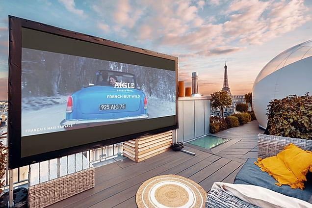 Ecran XXL de télévision qui diffuse le film de la maque AIGLE sur les toits parisiens