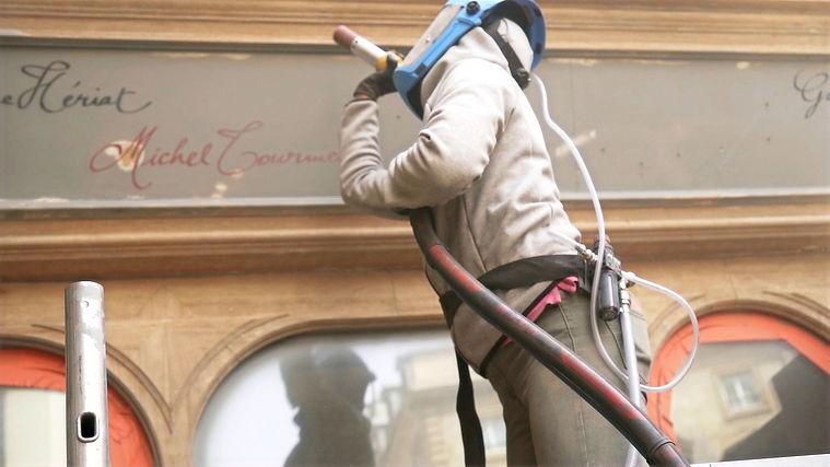 le COMPTOIR DE L'AÉROGOMMAGE entrain d'enlever les anciennes couches de peinture de l'Hôtel DROUANT à Paris, lors de sa réfection