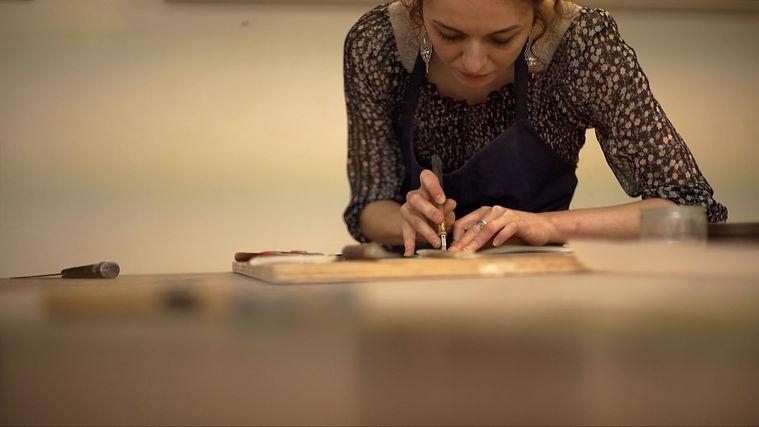 Marie Grillo atelier LA COULEUR DU VERRE ENTRAIN DE DÉCOUPER du verre sur sa table