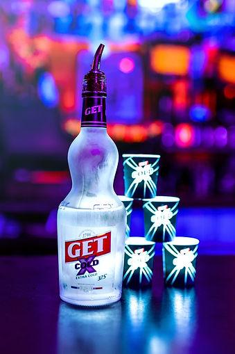 Flacon de GET X COLD et ses verres sur le comtpoir d'un bar de nuit
