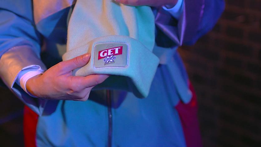 une animatrice x colder de get x cold montre un bonnet au logo de la marque