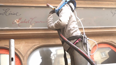 Un ouvrier sur une échelle en train de faire l'aérogommage sur la facade de l'Hôtel Drouant à Paris pendant sa réfection