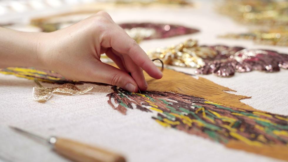 Main de la brodeuse Marie Berthouloux des ateliers ekceli en train de faire un point de peinture au fil sur une broderie XXL