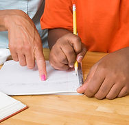 Female hand pointing to writing on notebook paper with another set of hands as if learning to read
